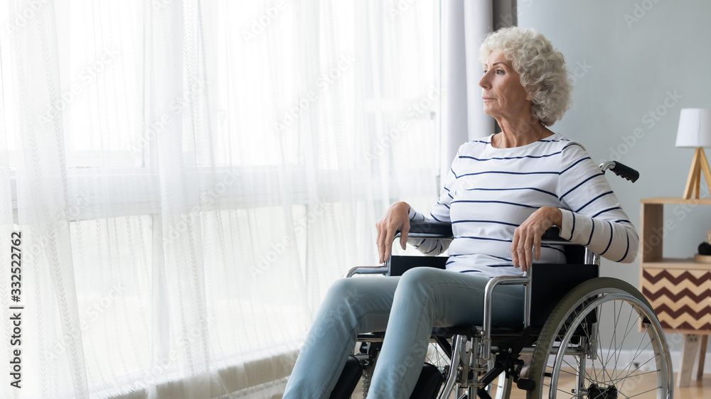 Fototapeta Pensive sick disabled old lady sit in wheelchair look in distance feel lonely at home or retirement house, thoughtful sad handicapped mature woman in wheel chair thinking, elderly disability concept