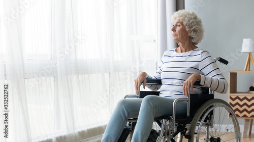 Fototapeta Pensive sick disabled old lady sit in wheelchair look in distance feel lonely at home or retirement house, thoughtful sad handicapped mature woman in wheel chair thinking, elderly disability concept obraz