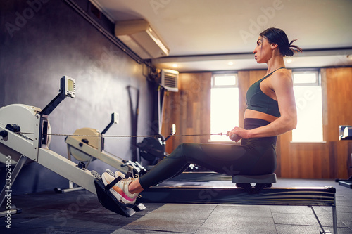 Obraz na plátně Determined young woman working out on row machine in fitness studio