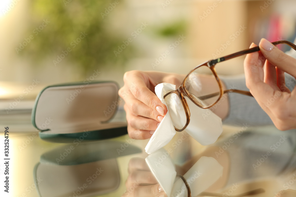 Fototapeta Woman hands cleaning glasses with tissue at home