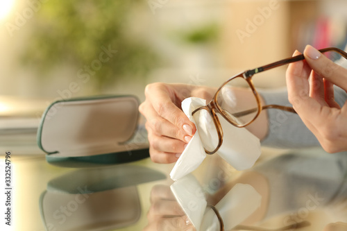 Obraz Woman hands cleaning glasses with tissue at home - fototapety do salonu