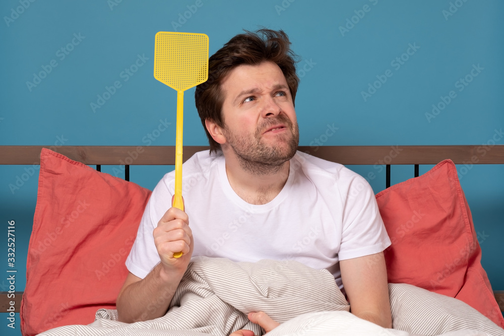 Fototapeta man holding a fly swatter wanting to kill annoying mosquito