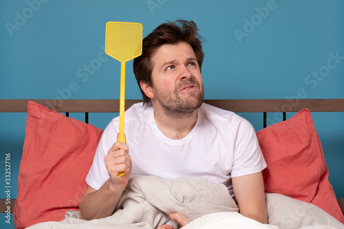 Photo man holding a fly swatter wanting to kill annoying mosquito