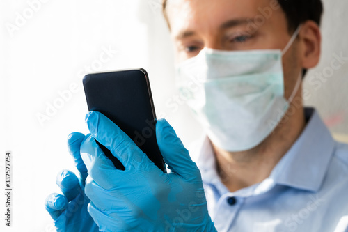 Man In Mask And Gloves Using Mobile Phone Canvas-taulu