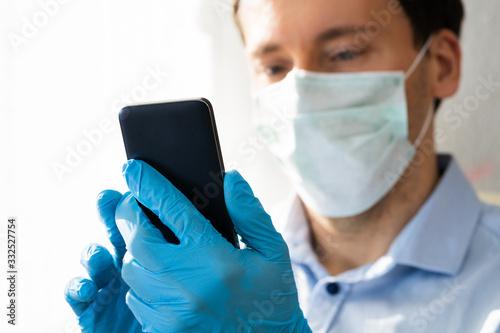 Fototapeta Man In Mask And Gloves Using Mobile Phone