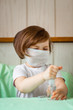 a little girl, in a medical mask , with a dysenfector in her hands, is being quarantined at home because of COVID-19
