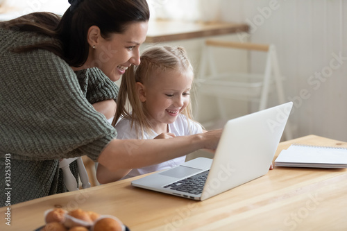 mata magnetyczna Happy young mother and cute preschooler daughter watch funny video on laptop together, smiling mom or nanny and little girl child have fun playing game on computer or studying learning online