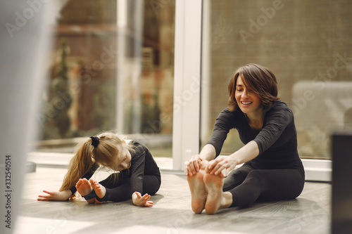 Fototapeta Girl is engaged in gymnastics. Family in a yoga studio. Kid in a black sportwear. obraz