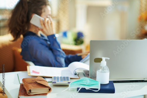 Fototapeta medical mask and hand disinfectant and woman talking on phone