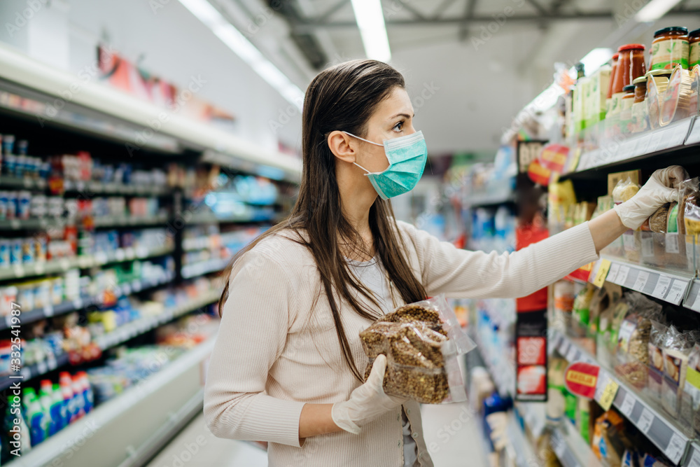 Fototapeta Shopping during an epidemic.Buyer wearing a protective mask.Nonperishable smart purchased household pantry groceries.Pandemic quarantine preparation.Dry goods and nutritional foods shopping.Expiration