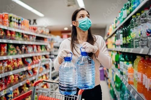 Fototapeta Woman wearing face mask buying bottled water in supermarket/drugstore with sold-out supplies.Prepper buying bulk supplies due to Covid-19 or Coronavirus and panic buying concept. obraz