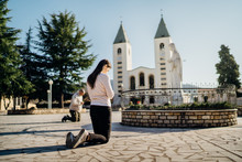 Religious Woman Praying To God And Virgin Mary In Medjugorje.Woman In Emotional Stress And Pain.Christianity.Strong Religion,faith And Hope Concept.Spiritual Healing.Enlightenment