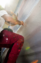 An Artist Working An A Mural With A Bright Sun Behind