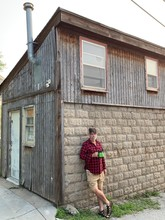 Leaning Against Wooden Shack.