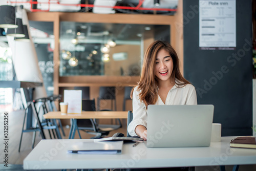 Fototapeta Happy young asian businesswoman sitting on her workplace in the office. Young woman working at laptop in the office. obraz