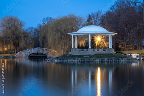 Fototapeta Night Closeup View of Hiawatha Lake Footbridge and Gazebo in Onondaga Park, Known Locally as Central Park in Syracuse, New York - One of the Most Visited Travel Destinations in Upstate New York