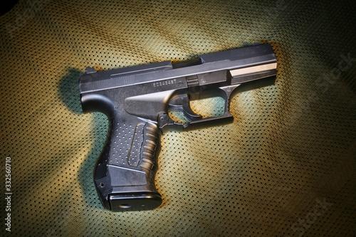 Photo Pistola de airsoft em cima de tecido verde militar