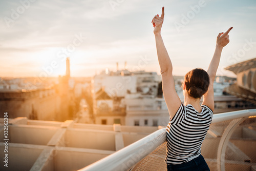 Cheerful happy spanish woman enjoying sunset from a cityscape viewpoint Wallpaper Mural