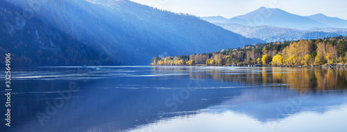 Fototapeta Panoramic view of autumn nature. The wide Yenisei River in Siberia. Blue sky, forested slopes and beautiful reflection. obraz