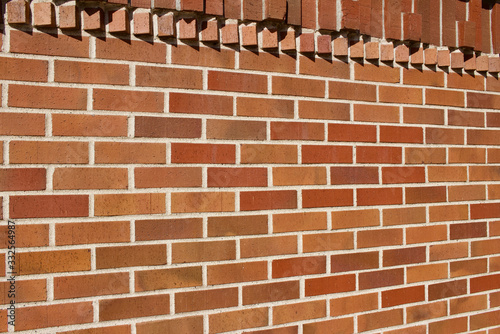Traditional red and brown brick wall texture background with rows of protruding bricks showing geometric brickwork designs (angle view)