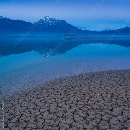 Fotografia, Obraz Trockenheit am Wasser und Berge - Forggensee in den Alpen von Bayern