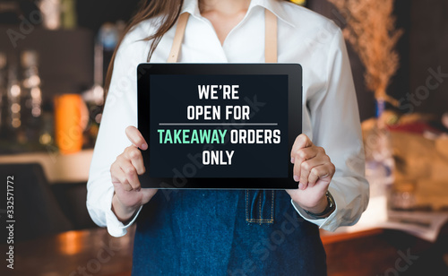asian barista holding tabblet sign we're open for takeaway orders only infront of counterbar.social distancing concept when coronavirus is outbreak in city