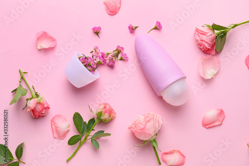 Photo Deodorant and flowers on color background