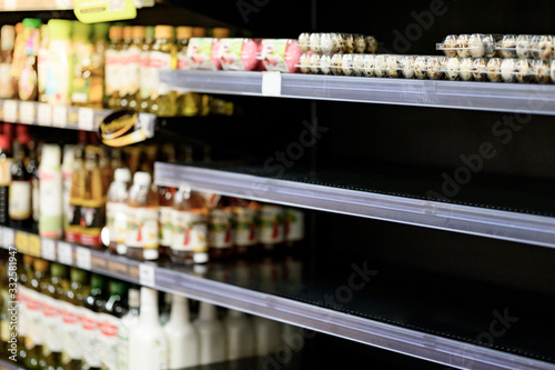 Fototapeta Empty egg shelves in a grocery store or supermarket. Hoarding food due to Coronavirus outbreak. Prepare food supplies for the worst case of COVID-19 pandemic. Stockpiling crisis all around the world. obraz