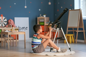 Little African-American boy with telescope looking at stars in evening