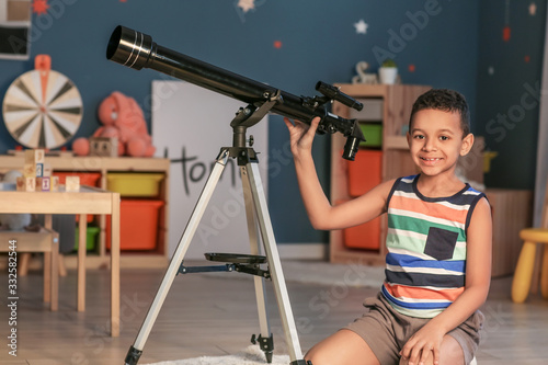 Fototapeta Little African-American boy with telescope looking at stars in evening obraz