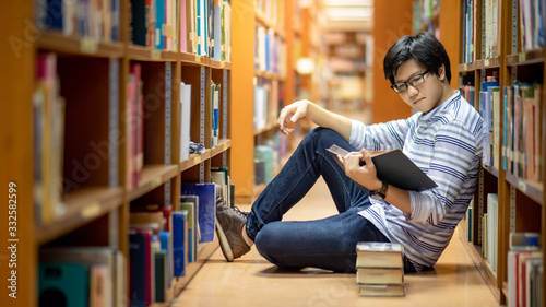 Obraz na płótnie Smart Asian man university student wearing glasses reading book by vintage bookshelf