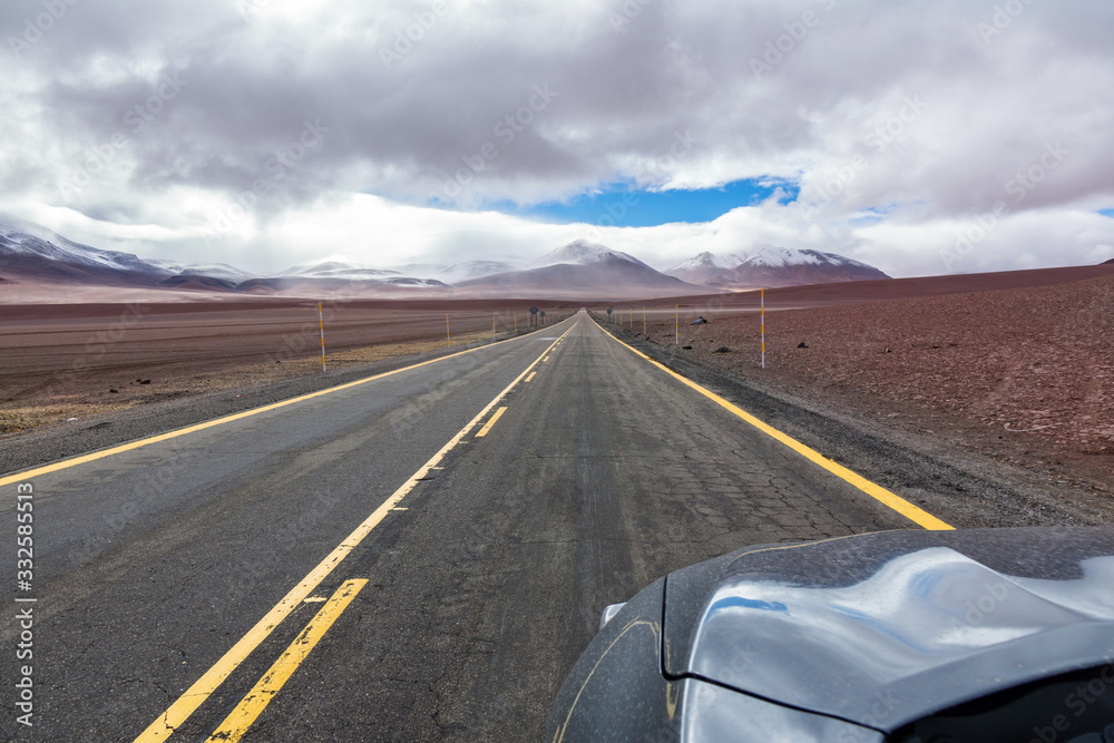 Fototapeta Road in Atacama desert savanna, mountains and volcano landscape, Chile, South America