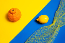 Whole Lemon And Mandarin Citrus Fruits With Yellow Mesh Packaging On Bright Abstract Color Block Background