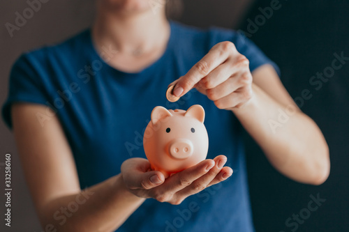 Fotografía female hands hold a pink piggy bank and puts a coin there