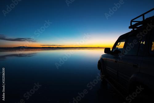 Photo Sunrise on Salar de Uyuni in Bolivia covered with water, car in salt flat desert