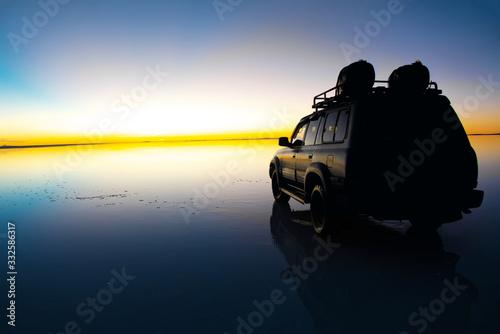 Sunrise on Salar de Uyuni in Bolivia covered with water, car in salt flat desert Wallpaper Mural