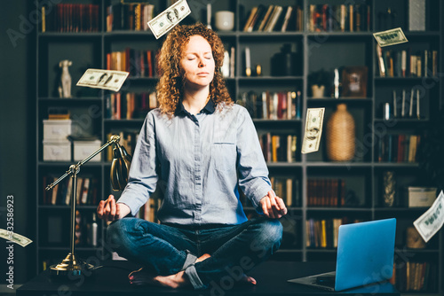 Photo Businesswoman doing yoga meditation with dollars banknotes flying in the air