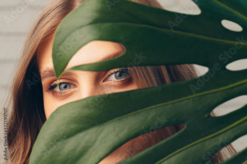 Photo Attractive young woman hiding behind monstera leaf