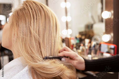Blonde girl in a beauty salon doing a hairstyle. Close-up.