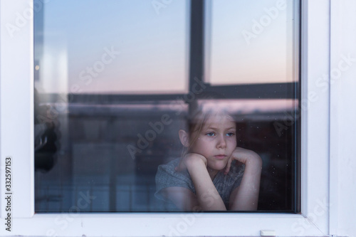 A sad, lonely child sits on the windowsill and looks out the window Fototapet