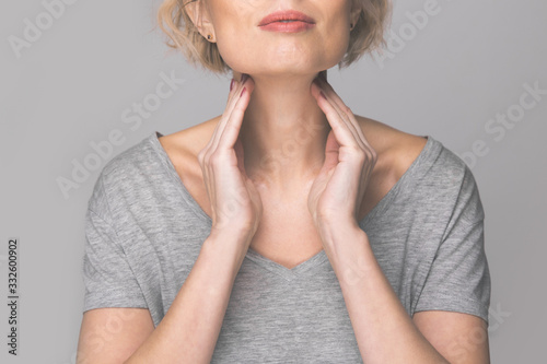 Fotomural Female checking thyroid gland by herself