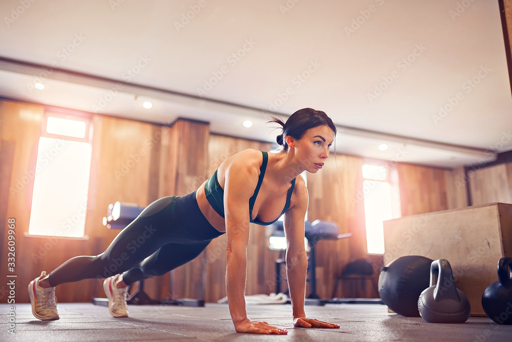 Fototapeta young motivated girl doing plank exercise at gym, full length photo, copy space.