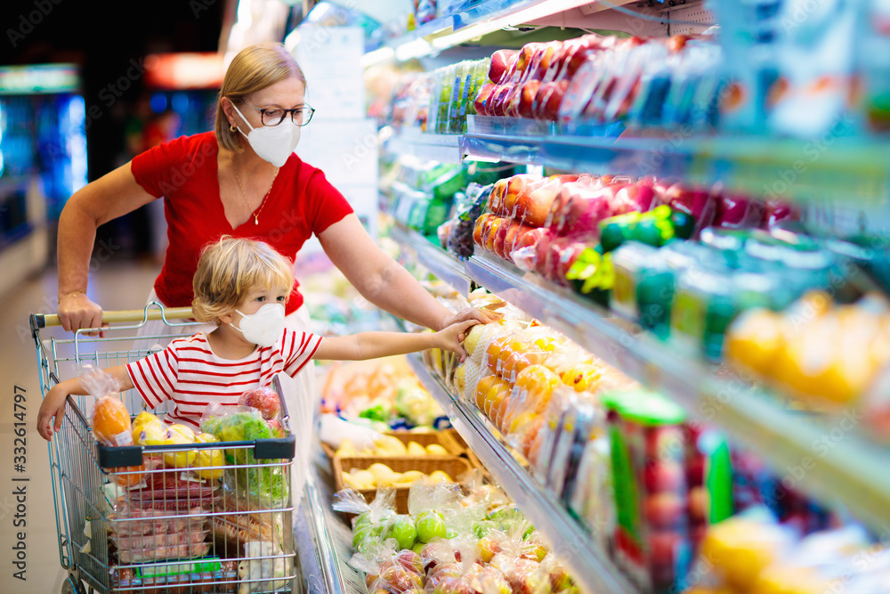 Fototapeta Mother and child buying fruit in supermarket.