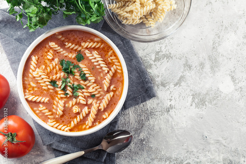 Obraz na plátně Tomato soup with fusilli pasta in the bowl