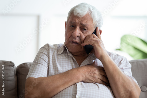 mata magnetyczna Upset older man touching chest, calling emergency, talking on phone, unhappy mature male having heart attack, lonely grandfather suffering from heartache disease at home, feeling pain, sitting alone