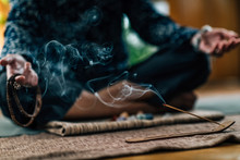 Mindful Woman Meditating With Burning Incense Sticks, Sitting In Lotus Pose. Hands In Lap, Palms Facing Upwards