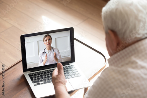 Close up older man talking with doctor by video call, using medical apps on lapt Fototapet