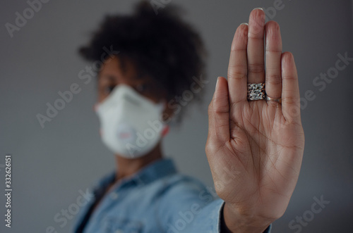 Fotografie, Tablou Black woman wearing a FFP3 mask and showing the palm of her hand as a stop gesture