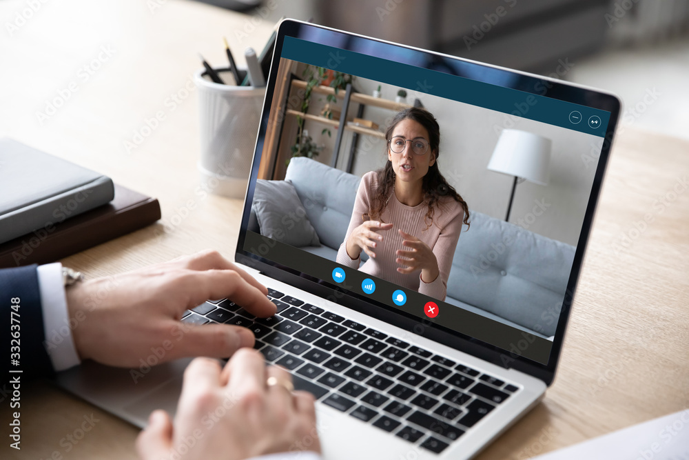 Fototapeta Close up of businessman talk with female business partner or client using video call on laptop, male employee talk consult with coach on webcam conference on computer, online consultation concept
