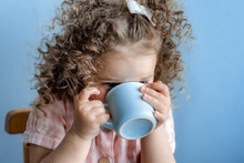 Little Curly-haired Girl In A Pink Dress Drinks Milk From A Blue Cup Of A Mug And Eats A Cupcake